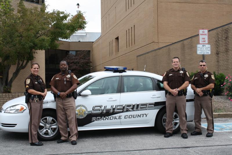 Four Sheriff Employees Standing in Front of Patrol Car